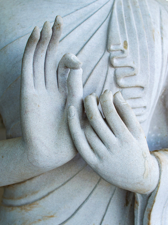 Detail of a white statue of the Buddha with his hands. Fingers in mudra. Stock Photo