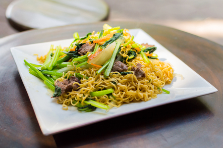 A Thai dish of chicken and noodles stir fry presented on a square white plate Stock Photo