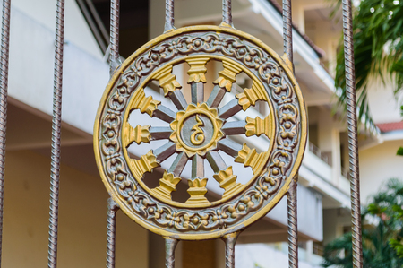 Golden stucco of the Wheel of the dharma and decorate by little blue glass, the dharma wheel, known as the dharmachakra, as a symbol in Buddhism. Stock Photo