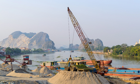 Barge loading sand by the crane. River in mountain region in Vietnam