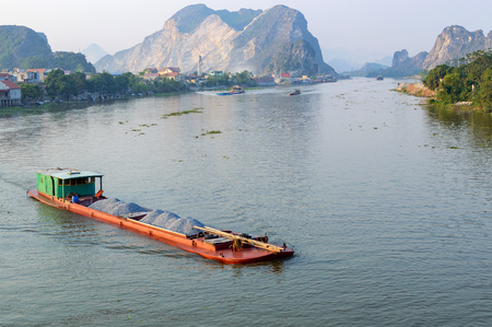 Barge with sand cargo moves on the river in mountain region of Vietnam