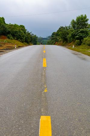 Asphalt Road op berggebied met gele lijn in het midden van de weg voor wegachtergrond of bedrijfsconcept. Donderwolken in de lucht.