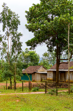 Wooden farm houses near with vegetable field in rural Vietnam.