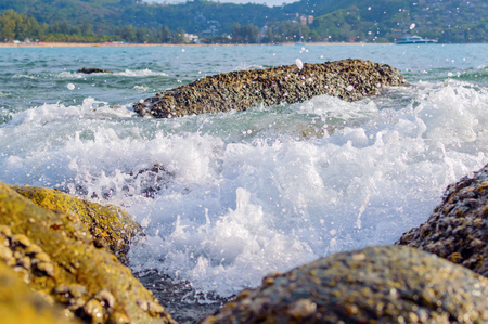 The waves breaking on a stony beach, forming a spray. Stock Photo