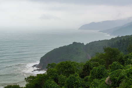 Hai Van pass - the famous road which leads along the coastline mountains near Da Nang city, Vietnam. Beautiful nature in nasty day with clouds on sky. Border between south and north Vietnam. View to the south, Danang city