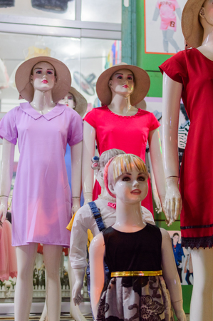 Female mannequins in hats inside a fashion store. Selective focus