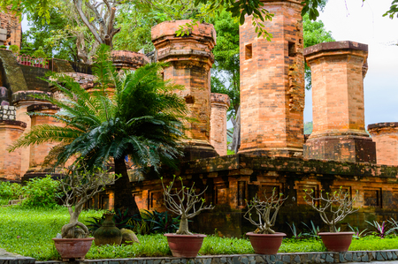 Garden Palm tree on foreground and old brick cham towers in Nha Trang, landmark Vietnam. Stock Photo
