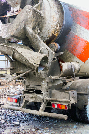 Concrete car mixer in transport position. The equipment is smeared with cement mixture.