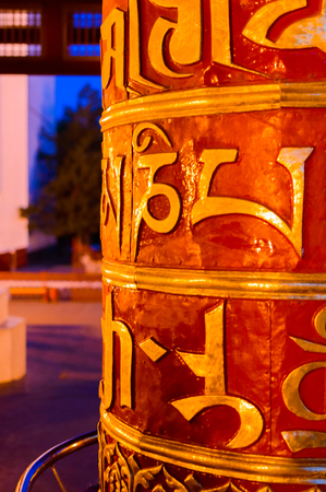 Religious Prayer Wheels With Sanskrit Symbols In Buddhist Temple