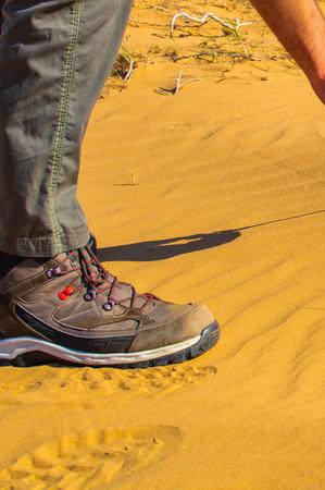 Hiker in sandy desert. Mens leg in boot on sand in desert. Tourist in a desert. Sandy background Stock Photo