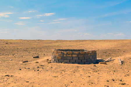 Old well in semi-desert. Concept of wasteland after apocalypse