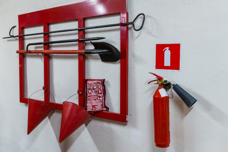 Red fire stand with fire extinguishing tools.