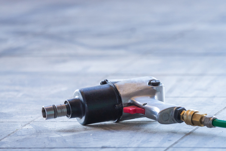 Pneumatic impact wrench gun in car service station Фото со стока