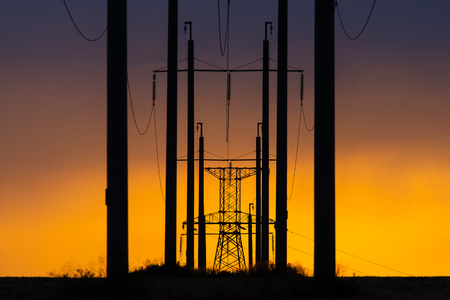 Rural landscape with high-voltage line on sunset. Dramatic sky view Banco de Imagens