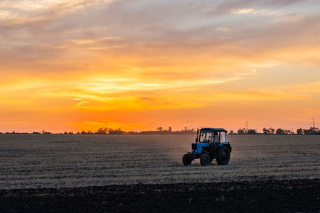 Agricultural machinery in the foreground carrying out work in the field on golden sunset. Stock Photo