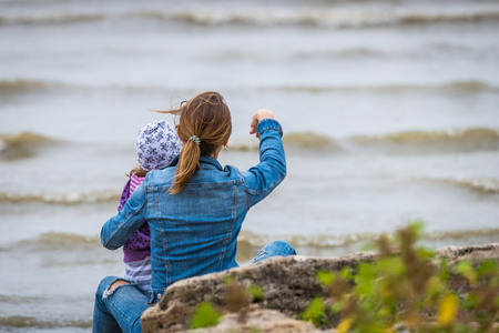 Back view of modern mother and child in colorful clothes on the beach throwing stones in seashore. Stock Photo