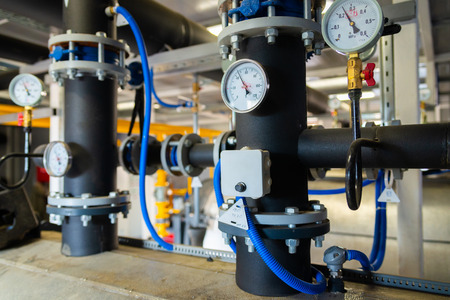 The equipment of the boiler-house, valves, tubes, pressure gauges, thermometer. Close up of manometer, pipe, flow meter, water pumps and valves of heating system in a boiler room.