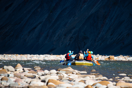Group of young people make a rafting on mountain river. Stock Photo