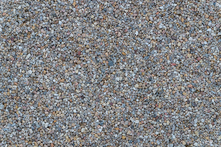 White granite gravel stones flooring pattern surface texture. Close-up of exterior natural material for design decoration background.