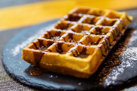 Waffle belga con sciroppo di cioccolato e zucchero a velo. Archivio Fotografico