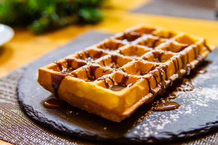 Belgian waffle with chocolate syrup and powdered sugar.