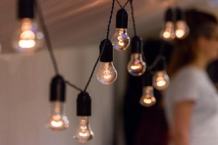 Nahaufnahme der dekorativen Vintage-Glühbirne, die drinnen an der Decke leuchtet. Transparente Lampen mit warmem Licht.
