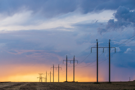 Rural landscape with high-voltage line on sunset. Dramatic sky view Zdjęcie Seryjne