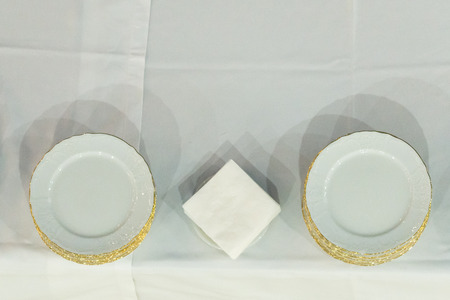 Empty white plates dish with gold trim on white table.