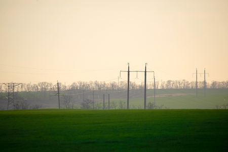 High voltage lines and power poles and green agricultural landscape during sunrise. Association of agriculture and industry in one photo. Beautiful spring landscape of the European plain. Zdjęcie Seryjne