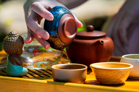 On the table on a wooden tray a teapot with tea, teapot, cups. Man, hands pouring tea. Zdjęcie Seryjne