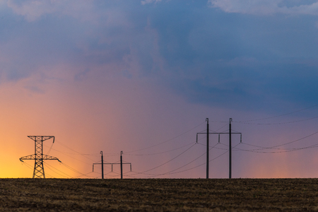 Epic sunset with rural landscape with high-voltage line.