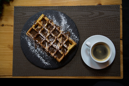 Cup of coffee and Belgian waffles with chocolate.