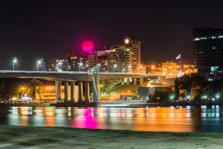 Sandy beach and bridge over the river and night city on the background