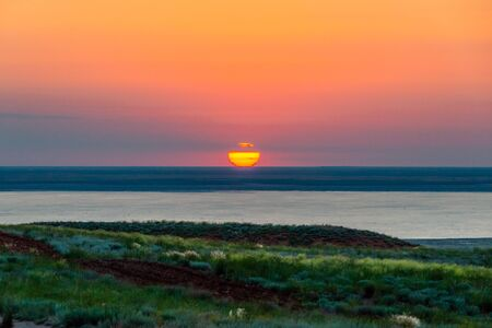 Beautiful bright red sunset over the lake and steppe. Banco de Imagens