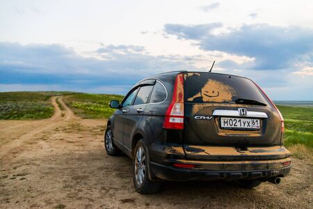 BASKUNCHAK, RUSSIA - MAY 28, 2019: Dusty Crossover Honda CRV SUV on rural road in steppe.