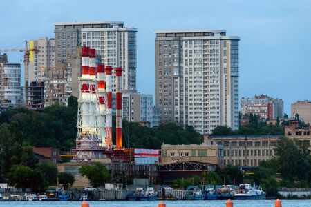 The chimneys of the boiler house building standing among multi storey residential houses. 版權商用圖片