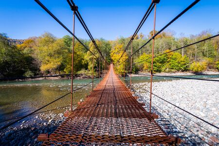 Narrow metal foot bridge across mountain river in autumn.