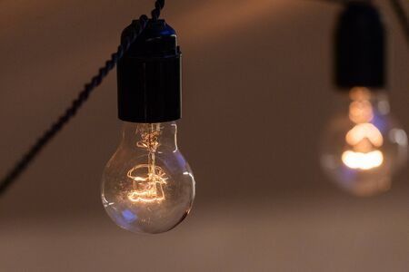 Close up view of vintage decorative light lamp bulb glowing on the ceiling indoors. Transparent lamps glowing with warm light. Zdjęcie Seryjne