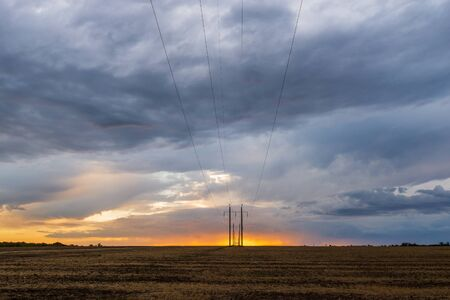 A row of high voltage electrical power lines cling to the horizon in an otherwise vast, wide open rural landscape on sunset with clouds.