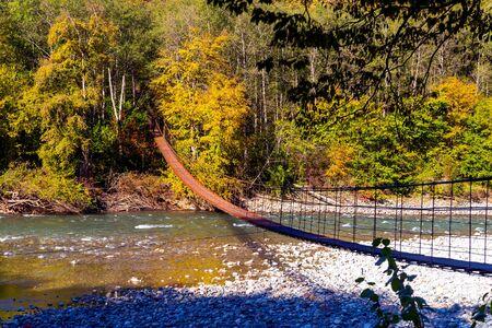 Narrow metal foot bridge across mountain river in autumn. Zdjęcie Seryjne