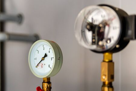The equipment of the boiler-house, - valves, tubes, pressure gauges, thermometer. Close up of manometer, pipe, flow meter, water pumps and valves of heating system in a boiler room.