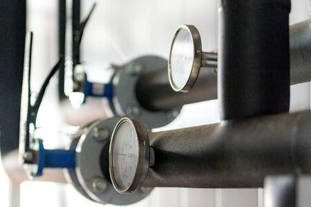 Die Ausrüstung des Kesselhauses, - Ventile, Rohre, Manometer, Thermometer. Nahaufnahme von Manometer, Rohr, Durchflussmesser, Wasserpumpen und Ventilen der Heizungsanlage in einem Heizraum. Standard-Bild