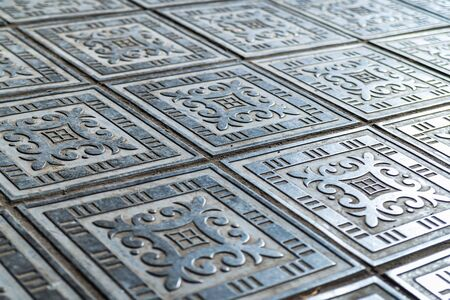 Patterns on large metal floor plates on a street of city. Imagens