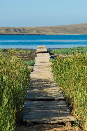 Old wooden jetty or pier at a lake or sea. Stock fotó