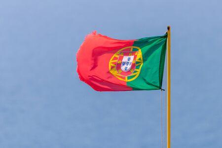 Flag of Portugal waving, against blue sky.