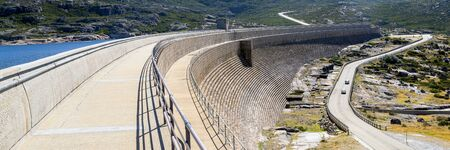 Dam on a mountain river and lake. Huge and long concrete construction. Reklamní fotografie