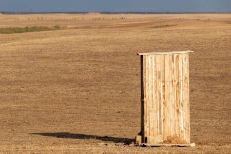 Photograph of an old rural outhouse or toilet in steppe. Single wooden building.