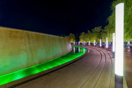 Walking path around fountain in resort with colored light illumination and trees on side at evening. Modern park design. Standard-Bild