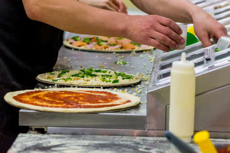 Cook in the kitchen putting the ingredients on the pizza. Pizza concept. Production and delivery of food. Standard-Bild