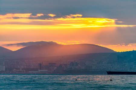 Cargo ship sailing the sea at a golden sunset or sunrise. Ocean shipment across water as the sun sets or rises. Harmony and beauty in nature. Scenic peaceful sea view.